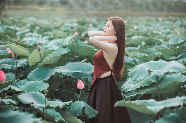woman in red and black dress surrounded by plant